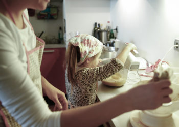 Mother and little girl spending quality time together in the kitchen, weighing and mixing ingredients for birthday cake, having fun. Family values, learning through inclusion concept.