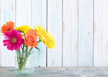 Assorted flowers over a wooden background