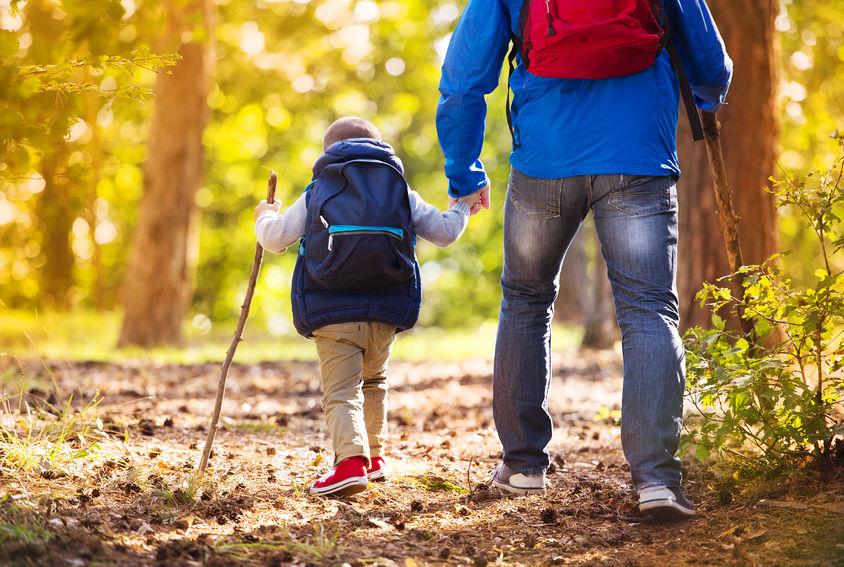 Un padre y su hijo practicando senderismo.