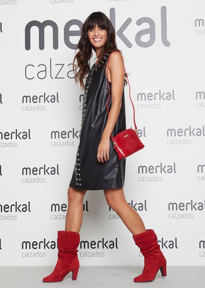 Ana Albadalejo con botas y bolso rojos combinados con un vestido negro.