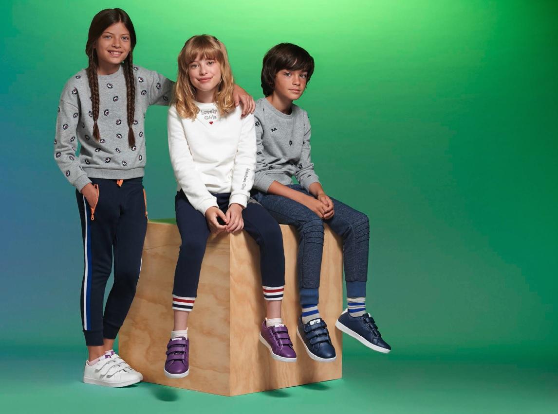 Tres niños con zapatillas deportivas preparados para hacer deporte.