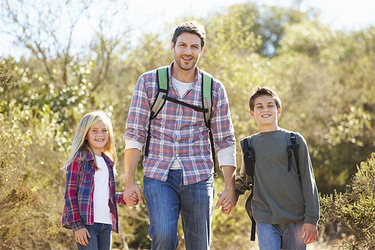 un padre con sus hijos de senderismo