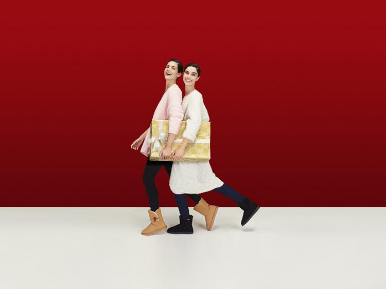 Dos mujeres sonríen mientras llevan sus regalos de Navidad
