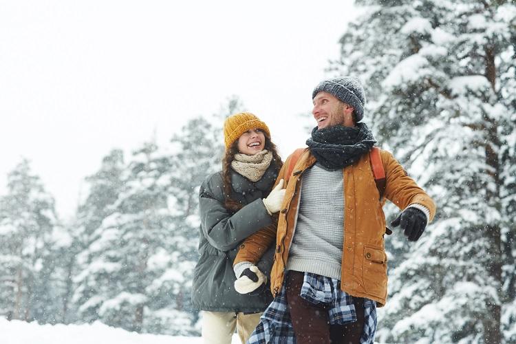 Pareja joven y feliz pasea por la naturaleza nevada en invierno